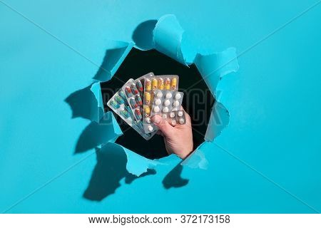 Assorted Pills Or Capsules With Medications In Hand Framed By Paper Hole. Mint Blue Trendy Torn Pape