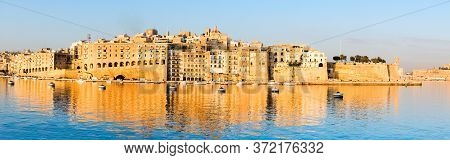 Valetta Harbor In The Morning, Senglea Peninsula In Morning Light With Reflection In Calm Waters Of