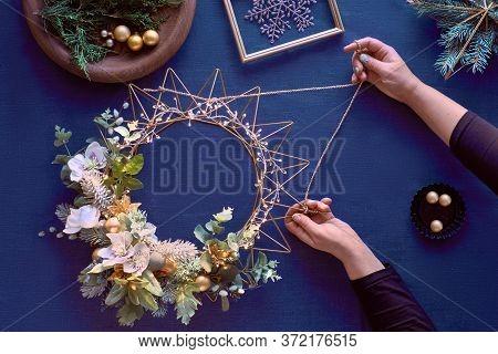 Making Of Decorative Christmas Wreath On Classic Blue Linen. Female Hands Make Handmade Wreath. Gold