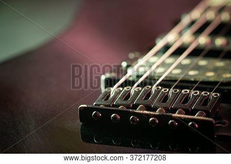 Rust Bridge Serves To Fasten Or Tighten The String. Black Vintage Electric Guitar In Dark. Closeup A