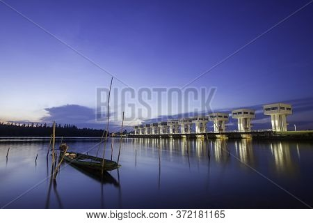 A Thai Folk Fishing Boat Made Of Wood, Moored On The Banks Of The River In The Morning