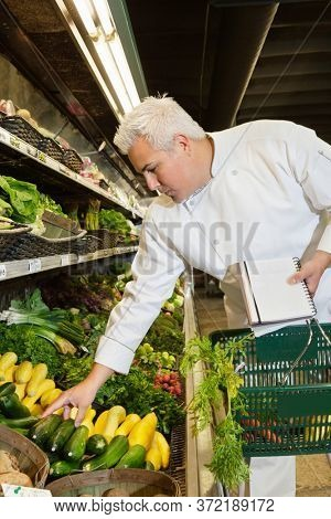 Mid adult chef looking at vegetables in market