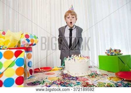Pre-teen birthday boy blowing candles on cake