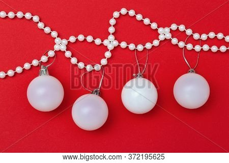 Christmas Decoration, Beautiful White Ball Close Up Handing On Pearl Beads Over Red Background With