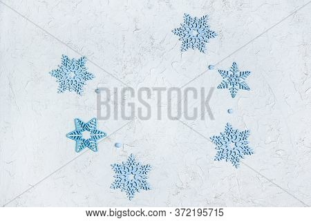 Openwork Wooden Blue Snowflakes On Light Shiny Background With Copy Space. Beautiful Decoration For