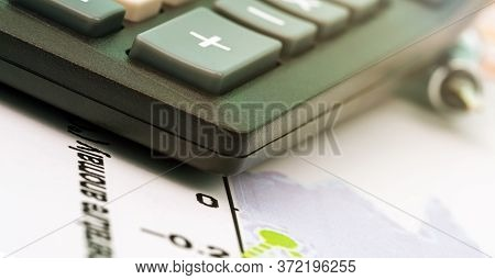 Black Outdated Calculator Edge With Sign Plus Lies On Sheet Of Paper Under Bright Electric Light Ext