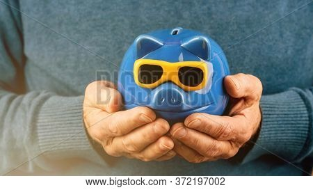Pensioner In Blue Woolen Pullover Holds Money Box Of Pig Shape With Yellow Sunglasses In Hands Under