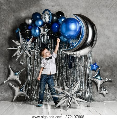 Frolic Kid Boy In Jeans White Shirt And Bow Tie Is Posing On Background Of Silver And Blue Metallic
