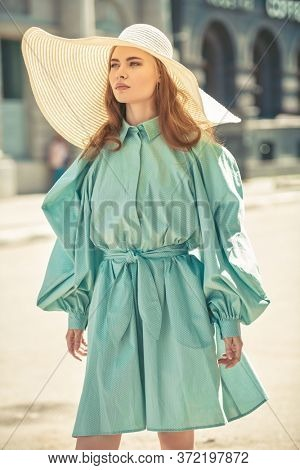 Portrait of a fashionable young woman in elegant summer dress and a wide brim hat standing on a city street. Summer fashion.