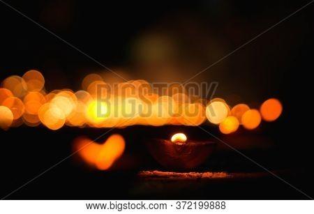 Hindu Festival Of Lights. Clay Diya Candle Illuminated. Traditional Oil Lamp On Dark Bokeh Backgroun