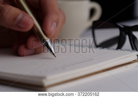 Close-up Of Hand Writing On A Notebook