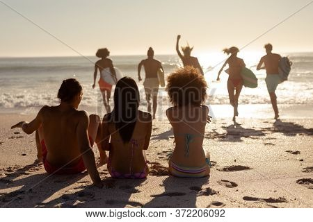 Rear view of a multi-ethnic group of three female friends on holiday sitting on a beach and watching their friends running into the sea holding surfboards as the sun goes down