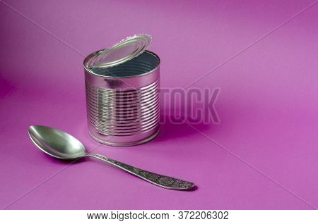 Empty Tin Can And Spoon On A Purple Background. Tin Can And Metal Spoon. Canned Food. Close-up. Copy