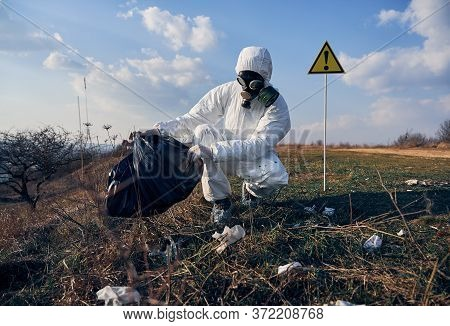 Ecologist Wearing White Protective Coverall, Gas Mask, Crouching Collects Plastic Garbage Into Black