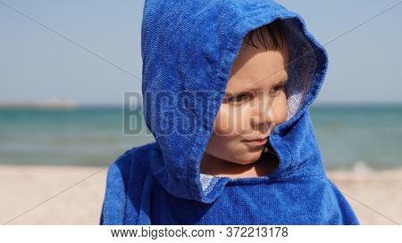 Close-up Portrait Of Glad Child In Blue Hood Of Bathrobe Standing On Sea Beach. Sea Coastline On Bac