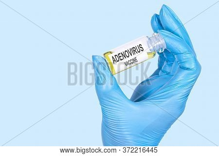 A Hand In A Blue Medical Glove On A Blue Background Holds A Bottle With The Inscription Adenovirus V