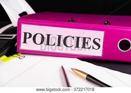 Text Policies Is Written On A Folder Lying On A Stack Of Papers With A Pen On The Table. Business Co