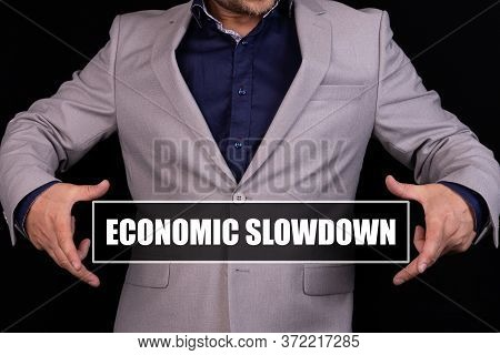 Economic Slowdown Text Is Written On The Background Of A Businessman In A Gray Suit. Business Concep