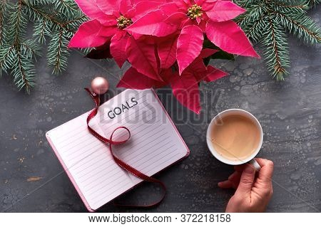 Christmas Goals Creative Flat Lay. Hand Holding Coffee, Notebook With Natural Xmas Decorations, Ribb