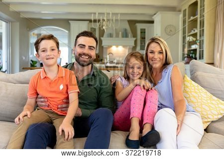 Caucasian couple and their children at home in the living room sitting on the couch smiling to camera, the father with their son sitting on his knee, and the mother with her arm around their daughter