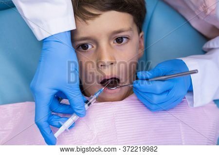 High angle view of dentist holding syringe while treating boy at medical clinic