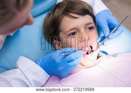High angle view of dentist examining boy at medical clinic