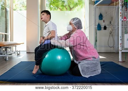 A Disabled Child Is On Top Of A Large Green Ball Doing Physical Therapy, Rehabilitation, Together Wi