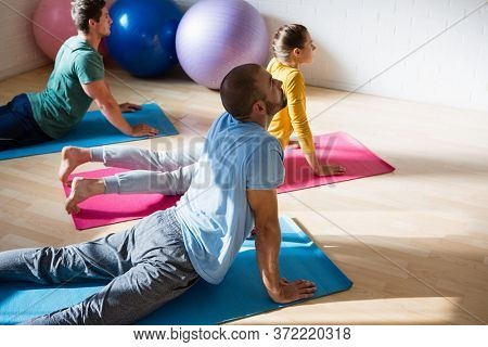 High angle view of yoga instructor with students practicing cobra pose in health club