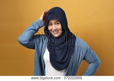 Asian Muslim Woman Wearing Hijab Smiling At Camera With Clumsy Expression, Scratch Her Head, Nervous