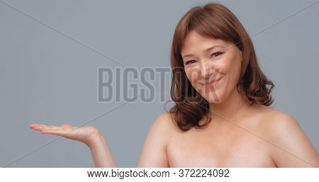 Beautiful Smiling Woman Advertises New Product. Red Haired Caucasian Woman Shows Her Hand Presenting