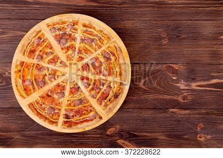 Sliced Salsiccia Pizza With Beef Sausages, Mozzarella, Various Sauces And Marinated Red Onions On Ro
