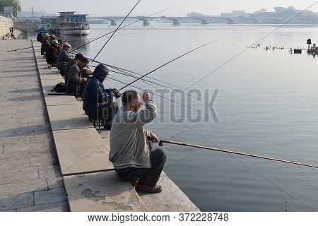 Pyongyang, North Korea - May 1, 2019: Local Fishermen Catch A Fish On Waterfront On Kim Il Sung Squa