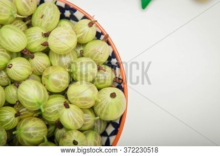 Green Berries Of Fresh Gooseberry, Summer Harvest Of Gooseberries, Leaves And Berry In A Bowl