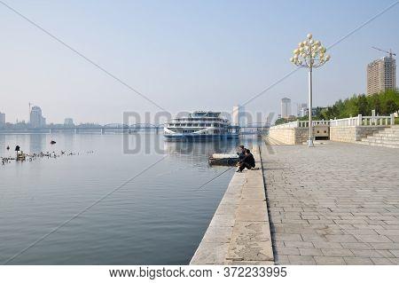 Pyongyang, North Korea - May 1, 2019: Street Scene. Two Fishermen Catch A Fish On Waterfront On Kim