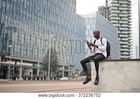 young man with smartphone in the city