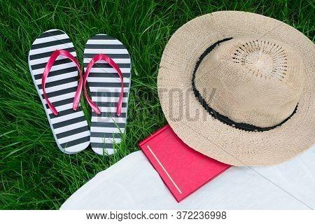 Sun Hat Book Flip Flops On Green Grass. Summer Vacation Concept.
