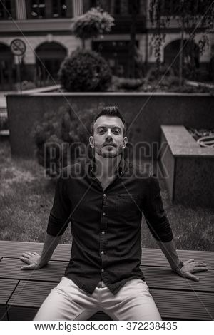 Young Man Sits And Ponders On Bench. Black And White Image.
