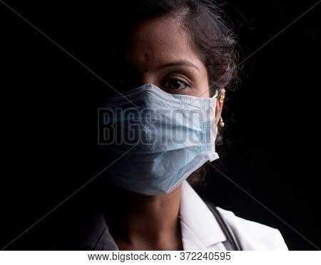 Close Up Of Professional Medical Doctor Or Nurse Protective Medical Facial Mask In Dark Room - Conce