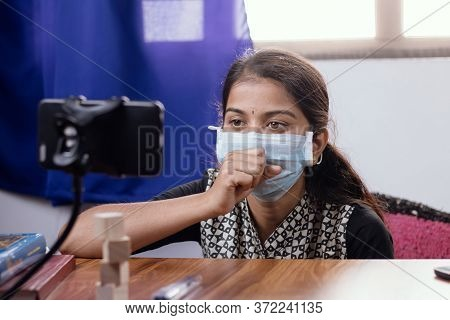 Young Girl In Medical Face Mask Talking Or Having Chat With Doctor In Video Conference On Mobile Pho