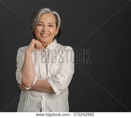 Happy Gray-haired Businesswoman Toothy Smiles At Camera. Beautiful Woman In Whiite Shirt Posing On G