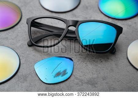 Closeup Of Broken Eyeglasses With Damaged Colored Lens Surrounded By Different Lenses On Table In Op