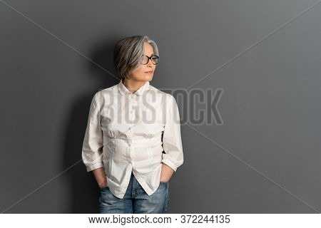 Beautiful Mature Lady In Glasses Stands Hands In Pockets Looking At Side. Elegant Gray-haired Woman