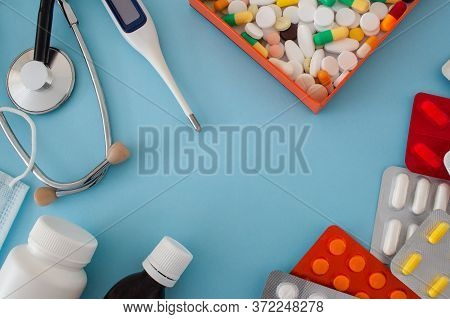 Colorful Tablets And Capsules In A Box, Thermometer, Statoscope, Medical Mask, Antiseptic Bottle, Co