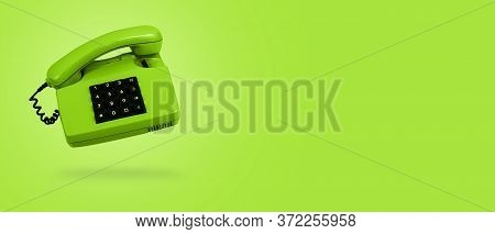 Vivid Green Old Landline Phone On Green Background. Banner. Copy Space. Hotline Phone, Call Center,
