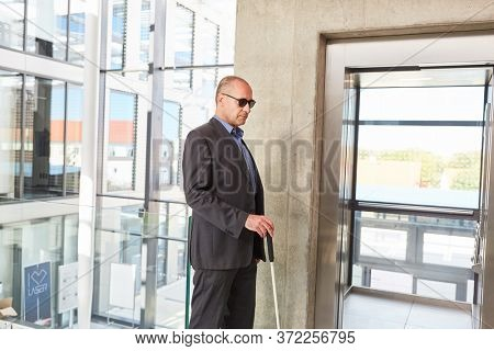 Blind senior man with glasses and cane in front of an elevator in the office building