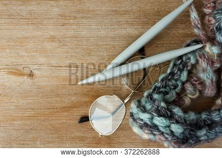 Multycolored Brown Turquoise Thread Clew Ball, Knitting Needles And Eyeglasses On Natural Wooden Bac