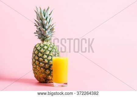 Fresh Ripe Pineapple And A Glass Of Pineapple Juice On A Pink Background. Hot Summer Concept. Copy S