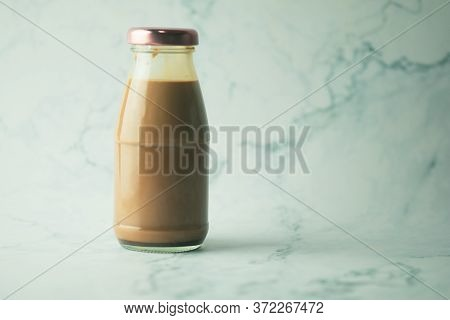 Cool Coffee Mocha In Glass Bottle On  A White Marble Background