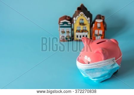 Piggy Bank With Medical Mask And Savings For Real Estate. Piggy Bank With House Models On Blue Backg