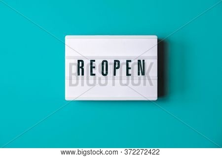 Signboard Reopen Of Lightbox On Turquoise Background. Reopen Sign Hanging On Blue Wall. Business Ope